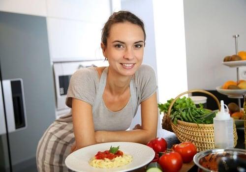 Woman in kitchen preparing pasta dish